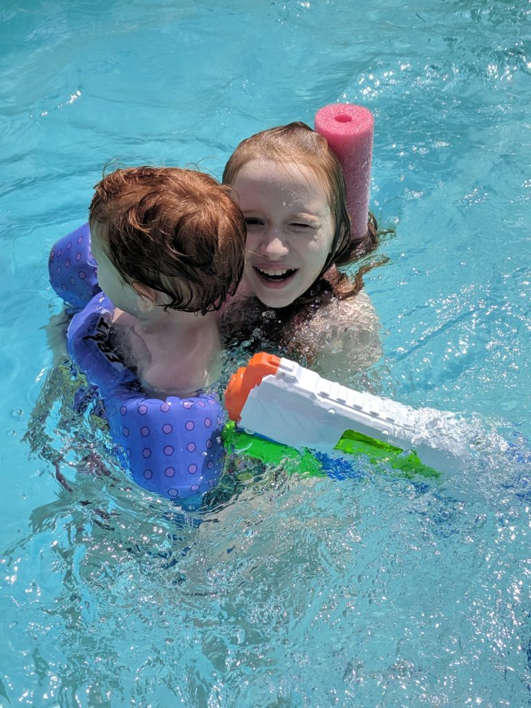 girl holding her little brother while swimming