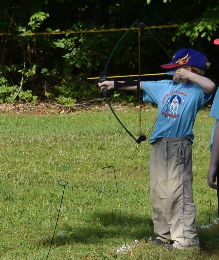 little boy shooting bow and arrow